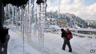 An Indian laborer walks carrying a cooking gas cylinder on a snow covered road in Shimla, India, Saturday, Jan. 19, 2013.