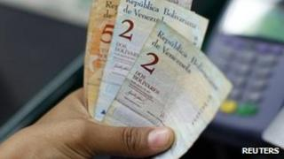 Cashier counts bolivar notes in Venezuela