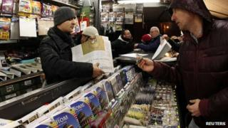 A news vendor sells a copy of the Osservatore Romano newspaper in Rome, 11 February 2013
