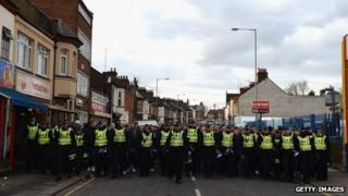 Police escort Millwall fans to the station following the match with Luton Town
