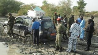 Cameroonian soldiers and officials surround the car from which a French family of seven were kidnapped