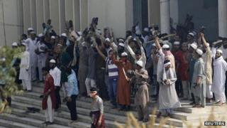 Activists from 12 Islamist parties stand at the entrance to the national mosque during a clash with the police