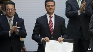 Mexico's president, Enrique Pena Nieto, shows signed education reform document
