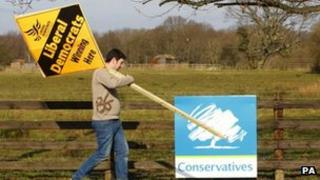 A Liberal Democrat supporter passes a Conservative Party placard