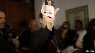Apostolic Nuncio to Mexico Christopher Pierre shows a portrait of Pope Benedict XVI during a farewell event organized by catholic worshipers in Mexico City