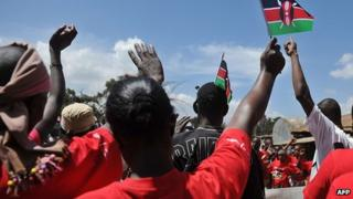 Youths participate in demonstration, waving Kenyan flags in the air