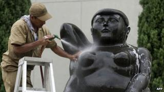 A city worker cleans a statue by Colombian artist Fernando Botero in Medellin