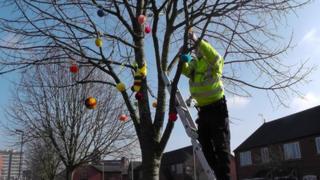 Police officer attaching pom-poms to a tree