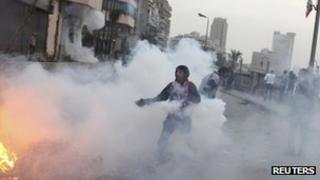 A protester runs with a tear gas canister in Cairo. File photo