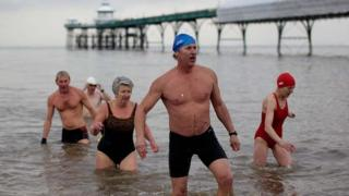 Swimmers leave the water next to Clevedon Pier.