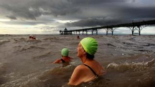 Swimmers in the water next to Clevedon Pier.