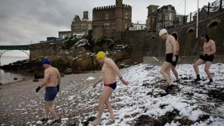 Clevedon sea swimmers walk down a snow covered beach.