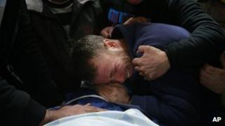 Palestinians relatives and friends cry next the dead body of Mohammed Asfour, 22, at the Ramallah Hospital in the West Bank city of Ramallah, 7 March 2013