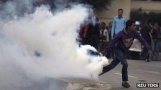 A protester throws a teargas canister in Cairo. Photo: 7 March 2012