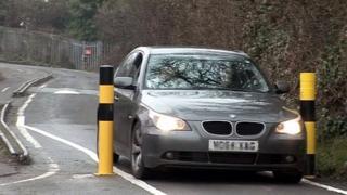 A car drives through the controversial bollards