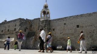 Tourists walk past the Church of the Nativity in Bethlehem