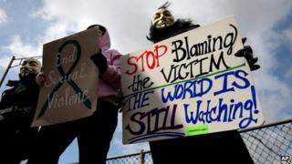 Protesters, who did not want to be identified, hold signs outside of the Jefferson County Justice Center and Jail in Steubenville, Ohio, on 13 March 2013