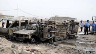 Iraqi police examine the wreckage after the deadly car bomb near Basra