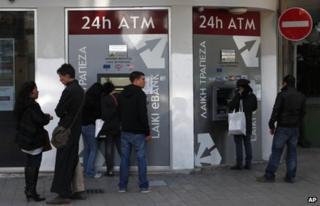 People queue outside a branch of Laiki Bank in Nicosia, Cyprus