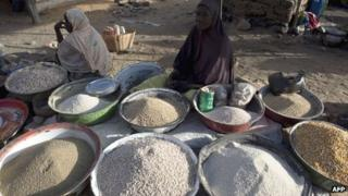 A woman waits for customers in a market in the northern city of Gao, on 13 March 2013