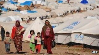 Syrian internally displaced people walk in the Atme camp, along the Turkish border