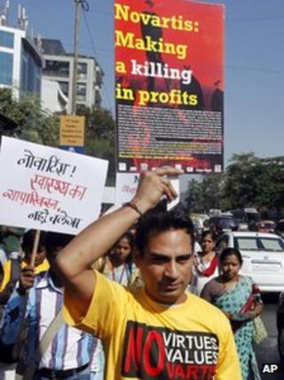 - In this Dec. 21, 2012 file photo, an Indian activist from a health group holds a placard while participating in a protest against Swiss drugmaker Novartis AG outside their office in Mumbai, India.