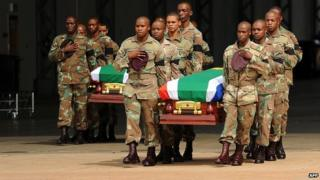 South African soldiers carry the coffins of their colleagues who died during a battle with rebels in the Central African Republic at Waterkloof Air Force Base in Pretoria on 28 March 2013