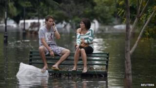 Residents sit on a bench in a flooded Buenos Aires street