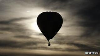 A hot air balloon is silhouetted at sunrise