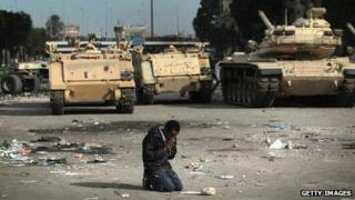 An anti-government demonstrator prays near Egyptian army vehicles on 3 February 2011 amid protests that eventually swept away the regime of Hosni Mubarak