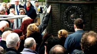 Families touch the Hillsborough Memorial