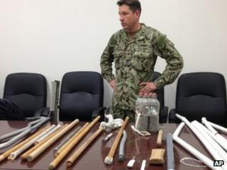 Navy Capt Robert Durand stands with makeshift weapons recovered from inmates after Saturday's clashes - 16 April