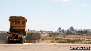 large mine truck dumps a load of coal onto a conveyer belt, in Moatize in northern Mozambique