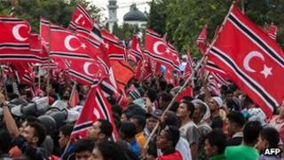Acehnese demonstrators wave banned separatist flags during a protest outside the palace guesthouse in Banda Aceh on 4 April 2013
