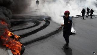 Riot police extinguish a row of burning tires set ablaze by Bahraini anti-government protesters, not pictured, on a street in Jidhafs, Bahrain, Sunday, April 21