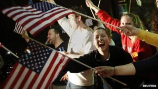 People wave US flags and cheer as police drive down Arlington Street in Watertown, Massachusetts on Friday following the capture of the second suspect in the Boston Marathon bombing, Dzhokhar Tsarnaev