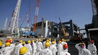 Journalists inspect damaged No.4 reactor building at Fukushima Daiichi nuclear power plant