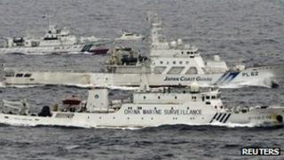 An aerial photo shows a Chinese marine surveillance ship Haijian No. 66 (C) cruising next to Japan Coast Guard patrol ships in the East China Sea, near known as Senkaku isles in Japan and Diaoyu islands in China, in this photo taken by Kyodo news agency on 23 April 2013