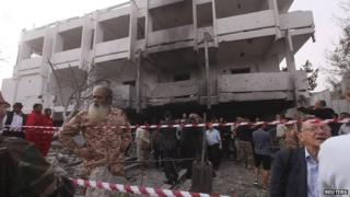 People stand among debris outside the French embassy after the building was attacked in Tripoli, 23 April 2013