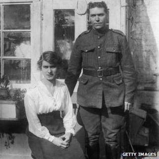 A British soldier and his wife posing for a portrait in their back yard, circa 1915