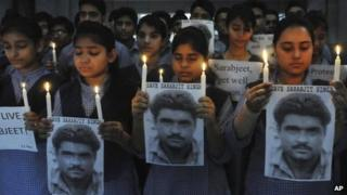 Indian school children hold photographs of Sarabjit Singh, an Indian spy on death row in Pakistan as they light candles and pray for his recovery in Amritsar, India, Monday, April 29, 2013