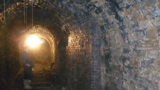 An archaeologist stands inside the tunnel at Fritchley