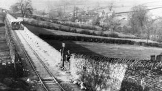 Two children sit on a wall waiting for a train in this black-and-white postcard from the 1930s.