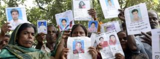 Relatives hold up portraits of those missing from the collapse of a garment factory in Savar, Bangladesh