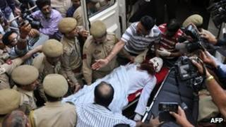 "Pakistani prisoner Sanaullah, an inmate of India""s central Jammu jail that was attacked by Indian inmates at a prison, is carried from a hospital to an ambulance in Jammu on May 3, 2013, before being transferred to a hospital in Chandigarh for treatment"