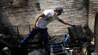 A resident combs through the remains of his home in Ecatpec, Mexico, on 7 May 2013
