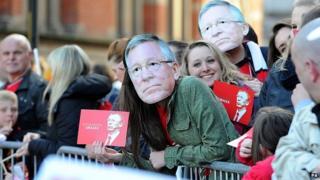 Fans in Sir Alex Ferguson masks in Albert Square
