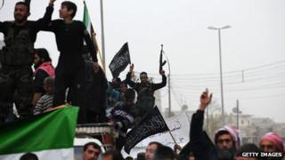 A Syrian rebel raises his weapon while waving an Islamist flag during an anti-regime protest in the northern city of Aleppo on March 22, 2013.
