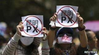 "Demonstrators hold up sheets of paper which read ""Kunming PX"" at a protest in Kunming on 16 May 2013"