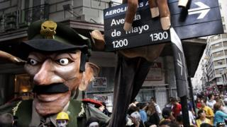 Demonstrators hold a figure representing Jorge Videla grabbing a street sign in Buenos Aires, 24 March 2006